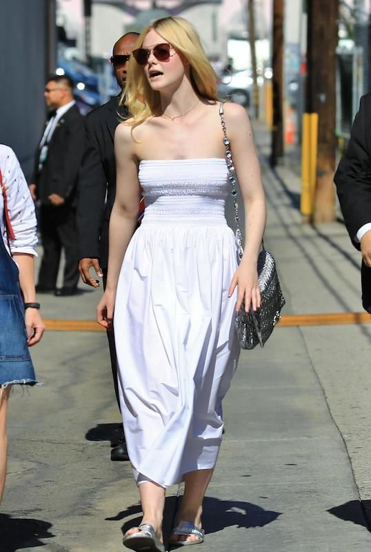 Elle Fanning wearing a midi length white strapless sundress with silver slip on sandals and a metallic chain strap bag