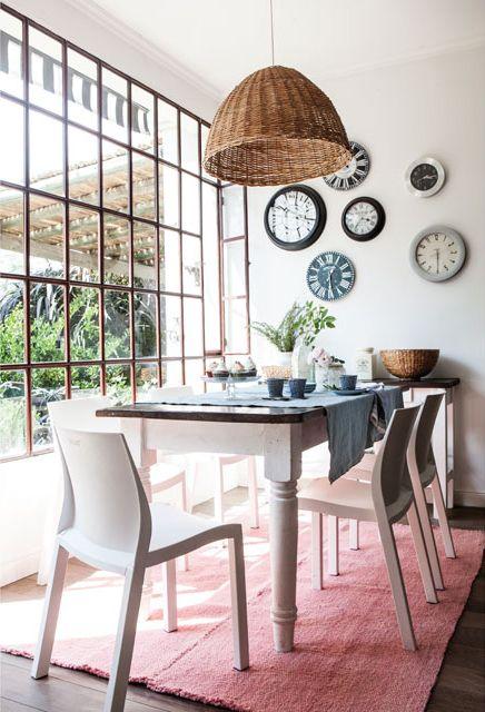 Ubicada frente a un gran ventanal de vidrio repartido, esta cocina se vale de detalles románticos y reminiscentes a los mercados parisinos. Destacan la gran lámpara de mimbre y relojes en la pared.