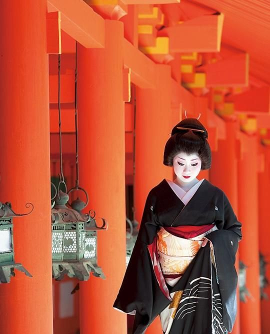 A geiko in crested kurotomesode.