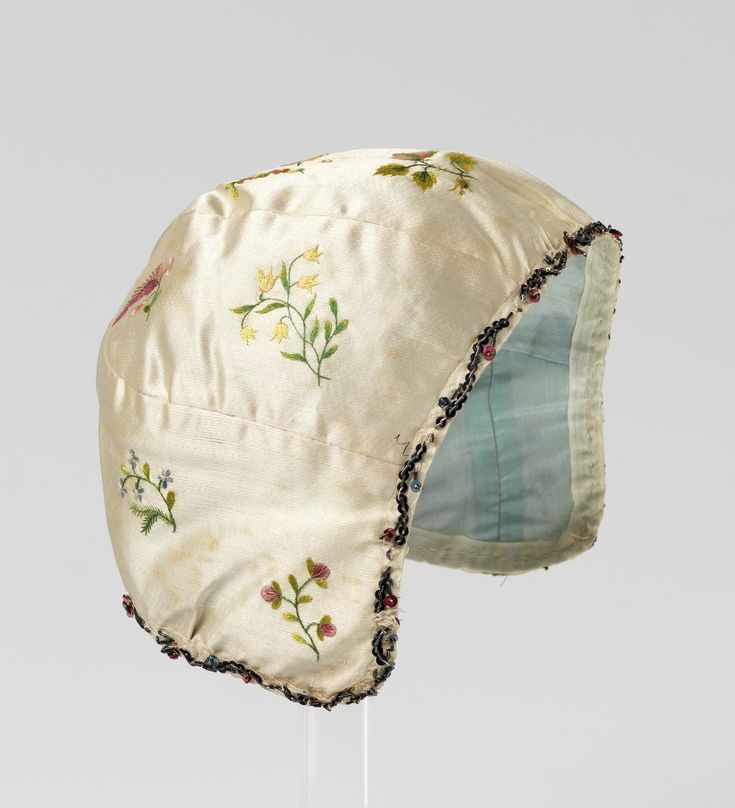 Child's cap, Norway, late 18th century. Cream silk satin embroidered with floral sprays, light blue silk lining.