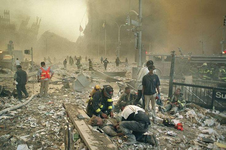 Bombeiros e paramédicos auxiliam feridos após os atentados terroristas ao World Trade Center, na Ilha de Manhattan, em Nova York. Na manhã do dia 11 de setembro de 2001, dois aviões comerciais foram sequestrados no Aeroporto de Boston por terroristas da Al Qaeda, e instantes depois atingiram intencionalmente as duas torres do maior complexo comercial do planeta