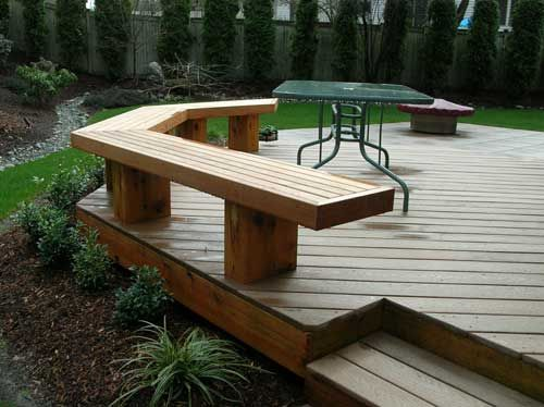 Use the bench as a railing Ground level wood deck with bench