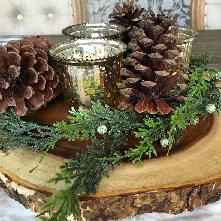 Wood slab centerpiece with mercury glass and pine cones © Rhiann Wynn-Nolet