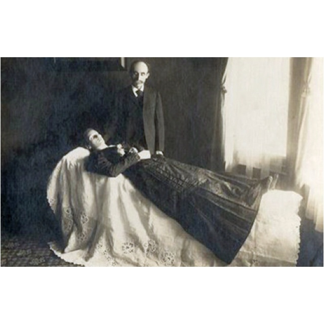 "Death, in Victorian England, was a grand and complicated business. There were many social rules in the classes who could afford it about mourning clothes, degrees of morning, and the length of time for which different mourning colours were to be worn.  A widow, for example, wore ""deep mourning"" (non-reflective black) for a year, including a full veil if she went outside. She then wore any colour black for another 9 months, then light mourning (including grey and purple) for another 3 to 6 months.  There was also a common custom, which seems distinctly odd today, of having photographs taken of the dead – sometimes on their own, sometimes in posed family groups, but all post-mortem photos.  In some cases, especially with children, there might well have been no other photographs for the family to keep. Photographs were expensive, and complicated to take and arrange, and therefore most people didn't have them done frequently. The death of a baby or child therefore often meant that the family had no photograph of the person at all, or no photograph taken with children born later than the one who had died.  But in other cases, it was part of a morbid fascination with death – the kind of behaviour that saw Queen Victoria go into black widow's clothes for 4 decades, from the time of her husband Prince Albert's death in 1860 until she died herself in 1901. Thus the photographs showing a young mother's children draped over her grave or tombstone, for example.  Some photos of the dead featured the person lying down, as if asleep. In others, the person was propped up, and even had his eyes painted in after the photo was taken. In these cases, the only way you can be sure which person is definitely dead is by noting that the face is very clear – the long exposures needed meant that living people tended to blur, slightly.Death Photos, Post Mortem Photography, Victorian Postmortem, Postmortem Photography, Moment Mori, Mementomori, Dead, Victorian Era, Memento Mori"