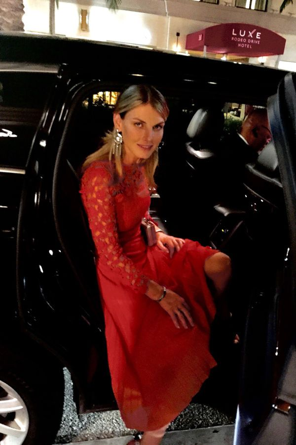 Channel Angela Lindvall's glamorous look this season with a long-sleeve red lace dress and sparkly statement earrings