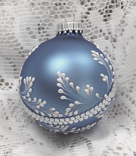 Soft Blue ornament with White 3D texture painted MUD design with added crystal rhinestone bling. Each ornament I create is a one-of-a-kind. The texture medium and paint brush I use to paint the ornaments were both created to my specifications. My signature M is located on the bottom of the ornament. Gift boxed. Measures 3 x 3 Ornament weight is 2 ounces.