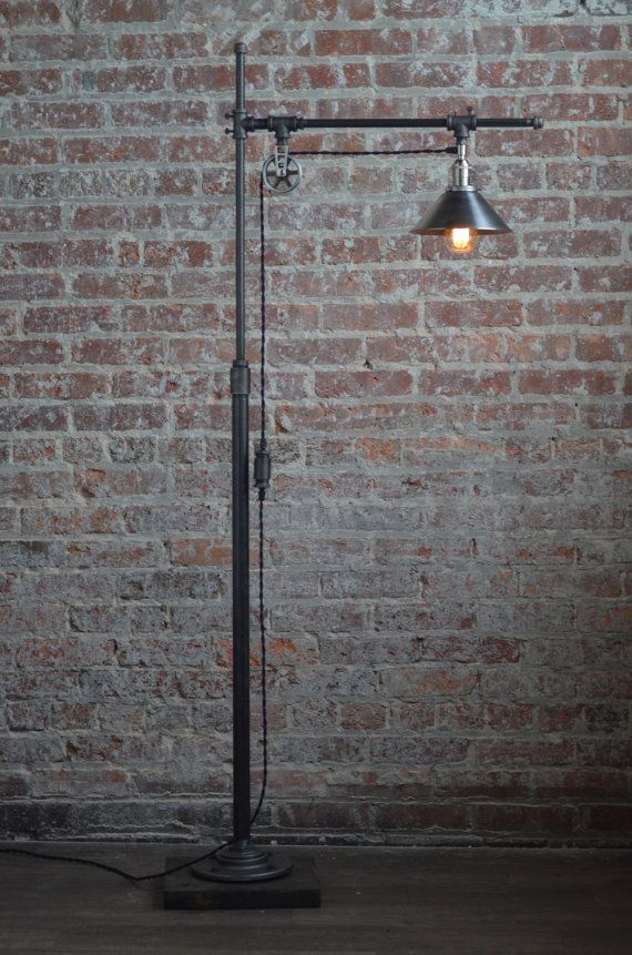 This industrial floor lamp features both a pulley and sliding arms to adjust the height and conformation of the lamp. By loosening the pins (by hand) you can move the shade front and back or raise and lower the entire arm to fit your desired height.  A 60 Watt Squirrel Cage Edison Bulb Hangs from the vintage style cord and offers warm ambient light. An 8 inch unfinished steel shade covers the bulb.  The fixture is constructed from industrial style black iron piping. The vintage bulb is easy…