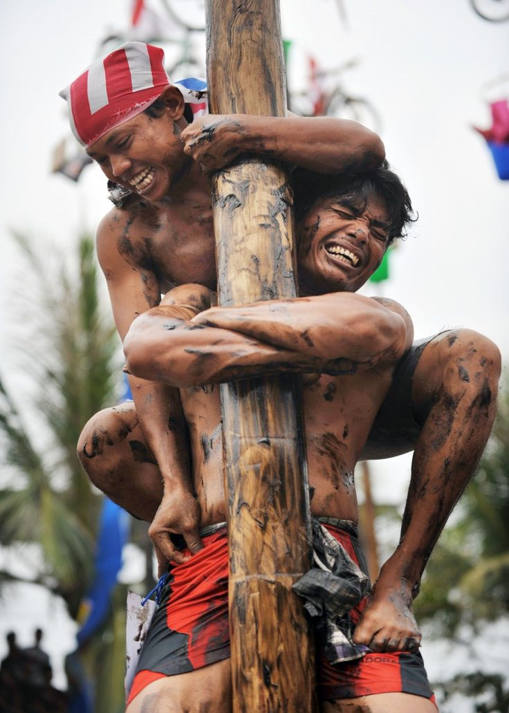 A man holds his friend as they attempt to climb a greased and slippery pole, to which is attached a prize, to celebrate the Indonesian Independence Day in Jakarta. Indonesia marked the 66th anniversary of its freedom from Dutch rule