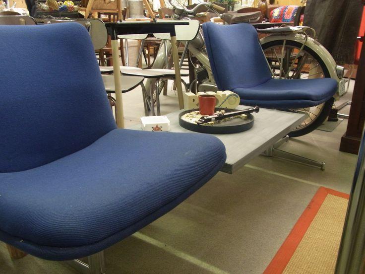 Bent u net voor uzelf begonnen en heeft u nog geen plek voor wachtende klanten? Wij hebben een onwijs leuk setje staan. De set bestaat uit 2 stoelen en een tafel in het midden. De set is geheel met elkaar verbonden en kan zo geplaatst worden. De stoelen zijn van blauw stof en de tafel is een grijs houten blad. Onderstel is van metaal. Lekker stevig. Afmeting is ongeveer 185 cm breed bij 60 cm diep. Prijs € 85.00.