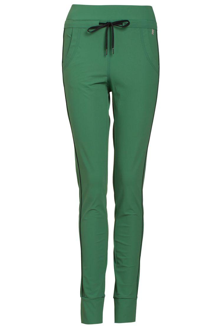 Sportieve broek van het merk Anna in de kleur groen. De broek heeft een elastische band om de taille en aan de onderzijde van de pijpen. De broek heeft een koordsluiting bij de taille en steekzakken aan beide zijden. De broek is afgewerkt met een zwarte bies aan beide zijden.