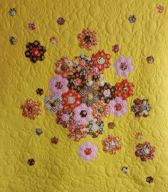 Hand pieced hexagons splashed over yellow fabric.  Machine Quilting by Susan Campbell.