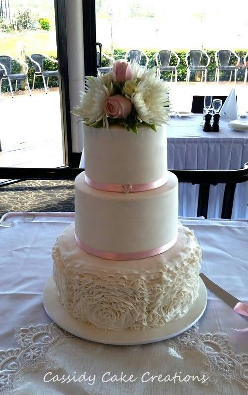 A rosette ruffle wedding cake finished off with fresh flowers