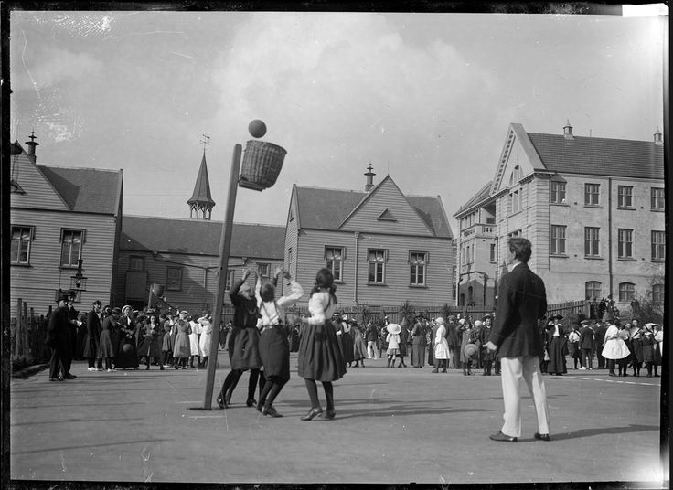 A game of basketball (later known as netball). Photograph shows a game in progress with the ball about to go into the basket (goal). In the background are spectators and unidentified school buildings. Taken by William A Price circa 1910. National Library of New Zealand