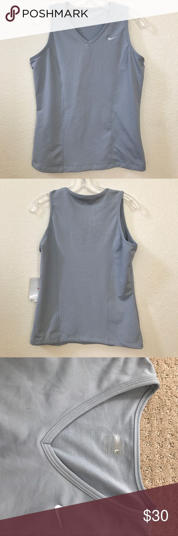 Nike Dri-Fit Ladies V-neck Training Tank size L Nike Dri-Fit Ladies V-neck Training Tank, in ladies size large (12-14). This silver gray tank top is made with Nike Dri-Fit fabric that wicks perspiration to keep you dry & comfortable. This tank top is 90% polyester & 10% spandex is quality made, woven with a soft & substantial feel. The v-neck cut & princess seam detailing make it wonderfully flattering. This Nike classic is certain to become one of your favorites for working out or leisure…