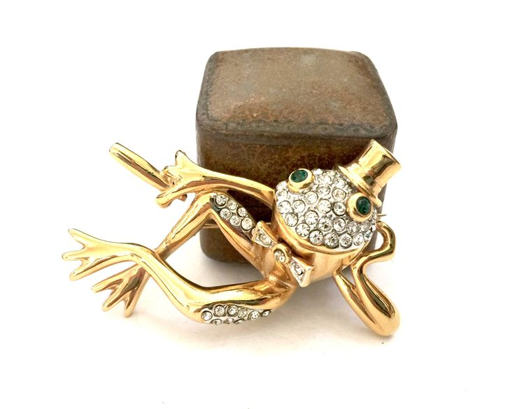 Charming Frog Brooch  This cute frog has a real ATTITUDE - hes just too cool Hes kicked back and yet dress for a party or show, with a top hat, bow tie, and a cigar (?) Composed in rich polished gold tone metal that is beautifully sculpted creating an adorable dimensional figural. Accented with sparkling pave ice crystals and green crystal eyes. This froggie is a real charmer and a great vintage brooch to add to any collection to wear and enjoy and the smiles hell bring.   Approx…
