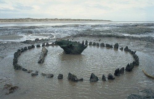 Holme Timber Circle (Seahenge), discovered on the beach at Holme, Norfolk in 1998. The circle of timber posts within the intertidal zone studied and was found to have been constructed in the spring/early summer of 2049 BC, during the Early Bronze Age. Because of the perceived threat of damage and erosion from the sea a rescue excavation was undertaken and the structure was entirely excavated/removed to a location inland, despite controversy.