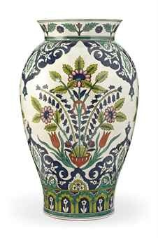 A LARGE IZNIK-STYLE POTTERY VASE SIGNED BATIGNONI, ITALY, FIRST HALF 20TH CENTURY Of baluster form with flaring rim, the painted decoration with floral sprays rising from a vase interspersed with cusped floral medallions, signed to the body and stamped at the base 21½in. (54cm.) high