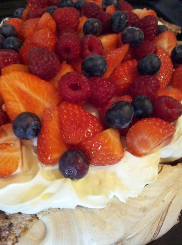 Pavlova cake with vanilla, whipped cream and fresh berries
