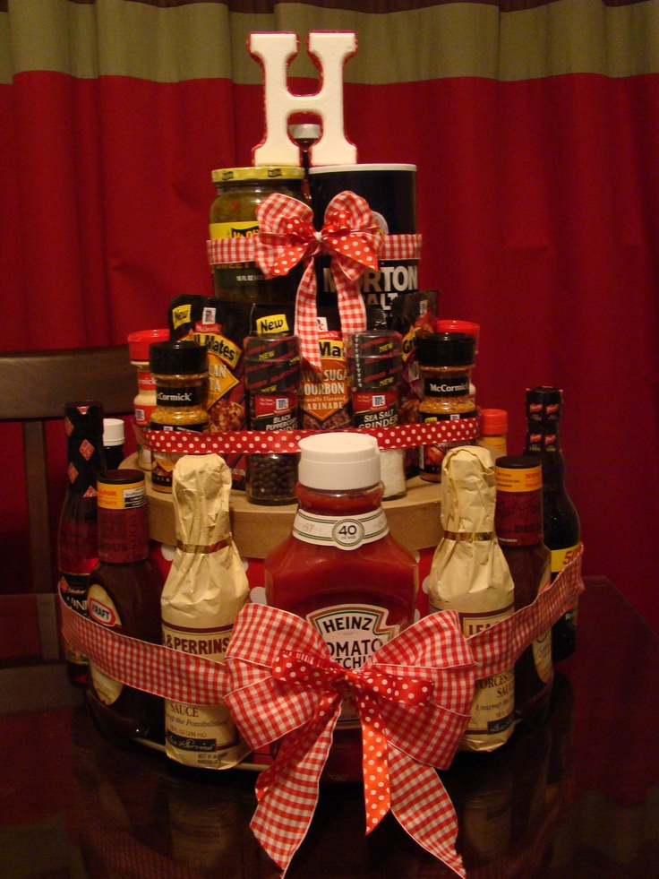 "This was a play on a diaper cake...I made it for a couple's grill and handyman shower. The layers were made with hat boxes in different sizes. The items were secured with a large elastic headband then covered with matching ribbon. The ""cake"" is topped off with an H for the couple's last name. If you use coupons and shop around Memorial Day and the Fourth of July you can get good prices on the condiments."