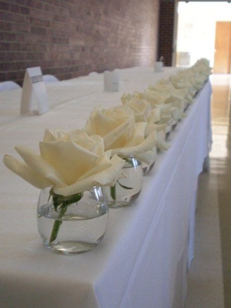 I like the idea of single blooms in tiny vases for extra floral - the cake table or the bar room tables etc