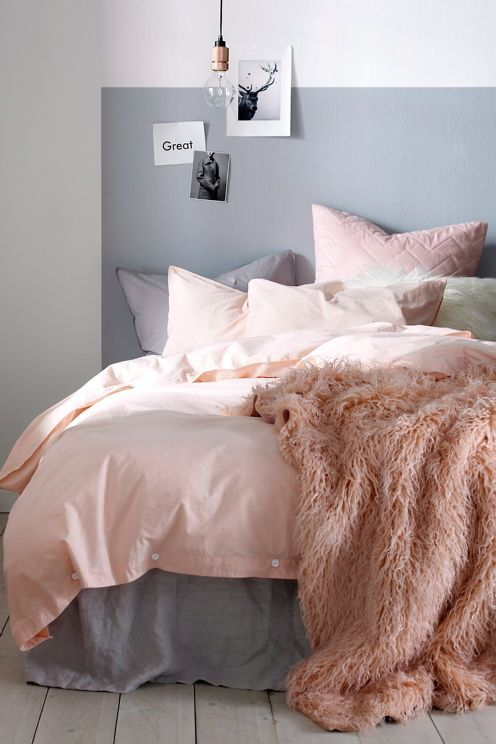 Gray sheets and a pink comforter. The fluffy blanket makes the room have a cozy feeling to it.