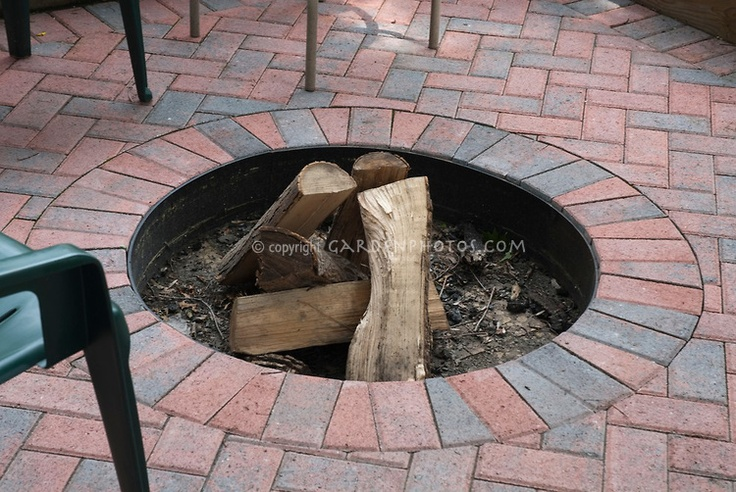 Firepit sunken into patio of circular laid brick pattern