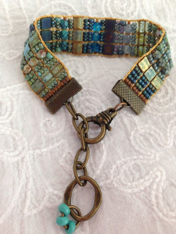 Many shades of blues, sage and mossy greens, hand loomed beaded bracelet that has adjustable closure. Tila, Czech and Picasso beads