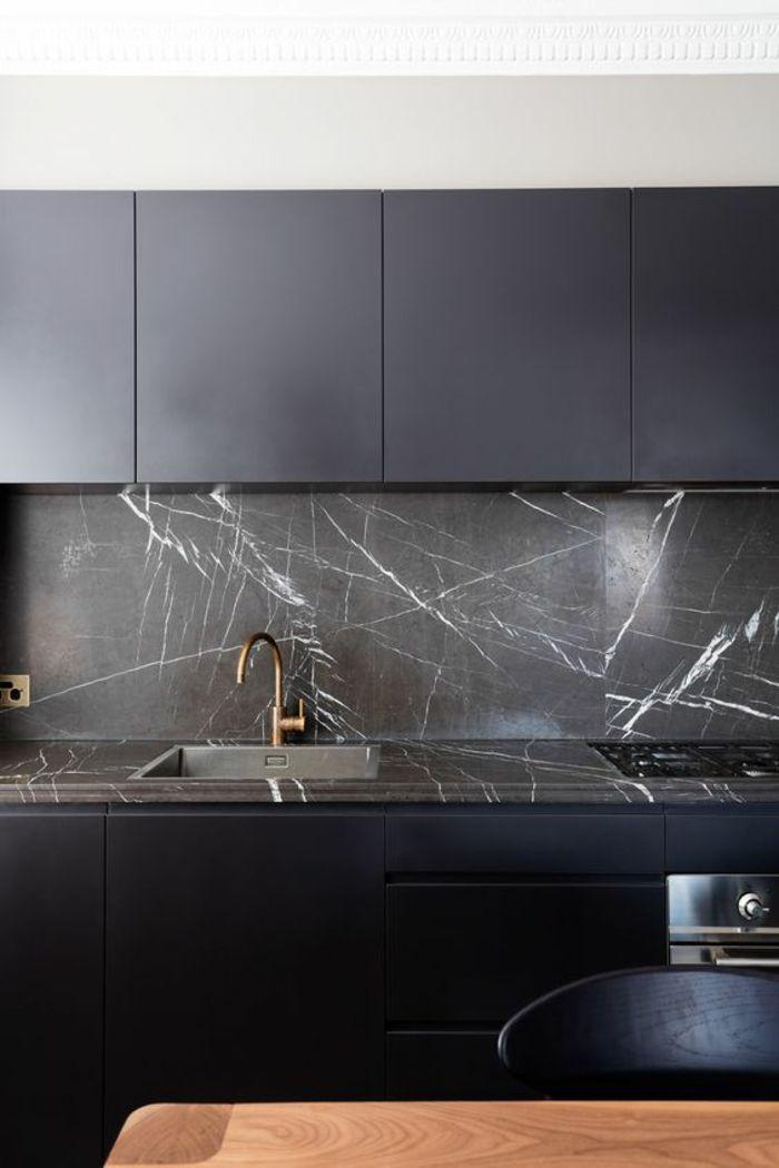 cuisine noir et bois avec mur au dessus du lavabo en matière imitation marbre noir