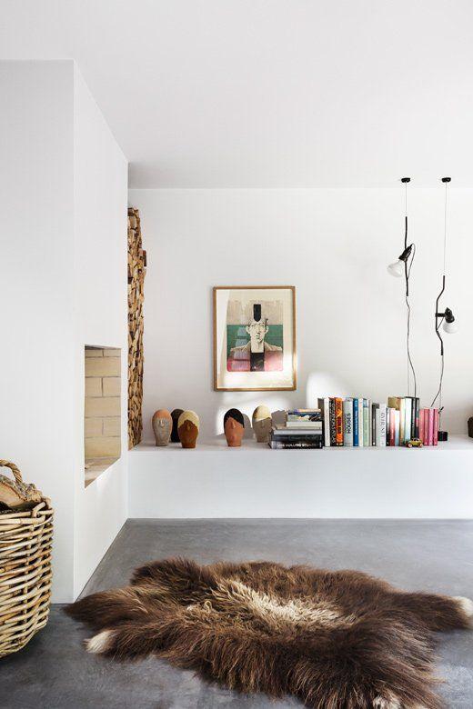 Der Wohnteufel steckt in den Details: Auch das Kaminzimmer im Haus des dänischen Fotografen Peter Krasilnikoffs besticht durch starke Kontraste. Ein puscheliges Fell trifft auf grauen Estrich, verspielte Kunst auf weiße Wände.