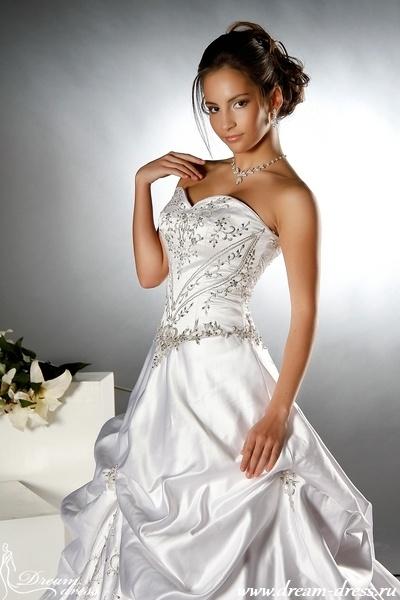 CAROLINA  Описание:  Данная модель сочетает в себе элегантность и богатую отделку. Платье выполнено в стиле А-силуэт. Верхняя часть платья плотно облегает фигуру и выполнена в виде корсета, что позволяет идеально подчеркнуть женскую талию. Драпировка юбки создана за счет отдельных украшений ручной работы и вышивки серебристой ниткой. С данной моделью хорошо будет сочетаться колье, широкий брильянтовый браслет и другие свадебные аксессуары. http://www.dream-dress.ru