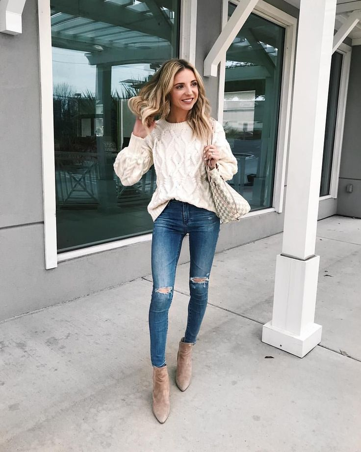 White cable knit sweater with trendy distressed denim blue jeans.