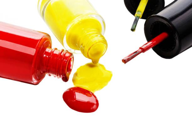 red and yellow nail polish is opened and spilled drops