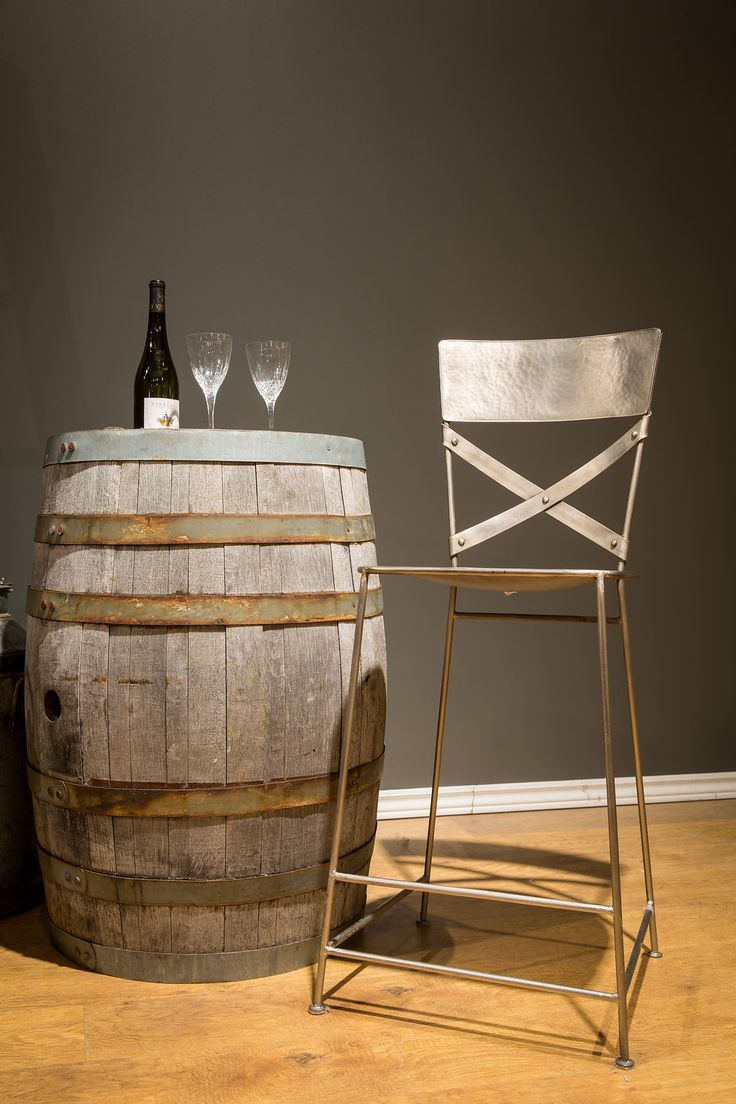 Repurposed wine barrels not only look great but can be used as a functional pub table when cozying up with these nickel stools.