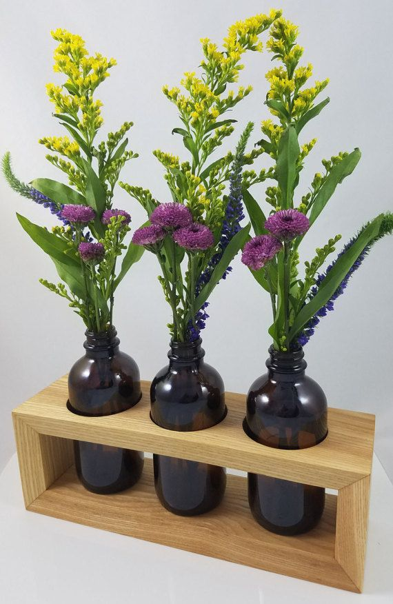 This handcrafted vase centerpiece and home decor item is made from solid White Ash. It is MEDIUM-SIZED and perfect for a dining table, side table, coffee table, or bookshelf; larger than a typical bud vase, but smaller than a full bouquet with the three 4 ounce bottles. What sets it apart are the beautifully-mitered corner joints that create the appealing waterfall effect as the wood grain flows from the top to the sides of the centerpiece. The edges of the frame are also delicately beveled…
