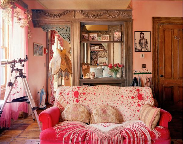 A nod to a bygone era. The details like the shawl on the sofa, fringed lamp, ornate carved wood all help to create a moment in time.. I love this colourful room.