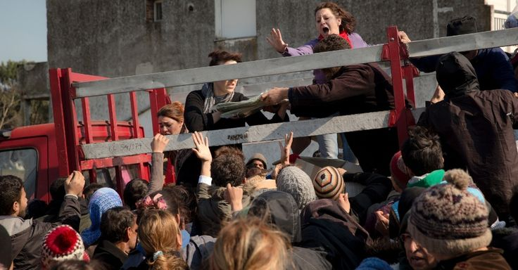 20160319 - Mulher grita para acalmar imigrantes desesperados que cercavam um caminhão que distrubuía cobertores e mantimentos em Idomeni, na fronteira da Grécia com a Macedônia Vadim PICTURE:Ghirda/AP