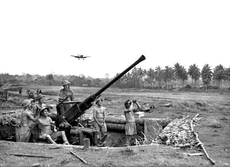 Australian soldiers of the 2/9th Light Anti-Aircraft Battery, Royal Australian Artillery position a  Bofors 40 mm anti-aircraft/multi-purpose autocannon at a possible enemy Imperial Japanese plane during the Battle of Milne Bay, Papua, September 1942
