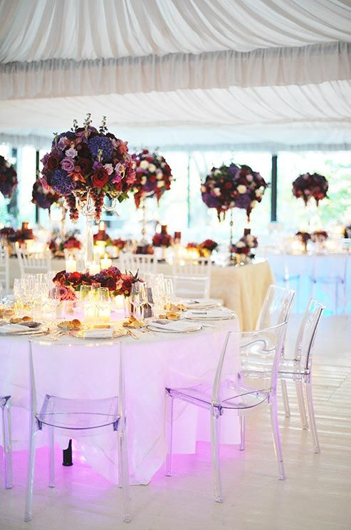 Clear chairs and white tablecloths provide a clean canvas for ornate centerpieces and lights glowing from beneath the tables.