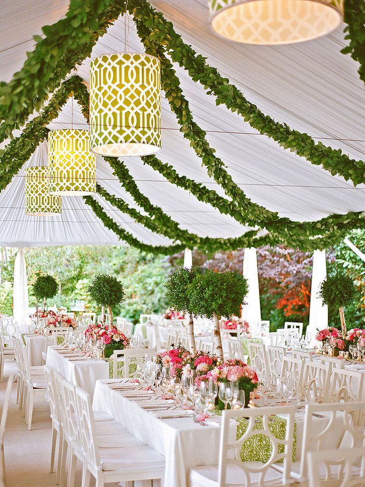 Outdoor wedding tent with mini tree centerpieces, lamps and hanging garlands