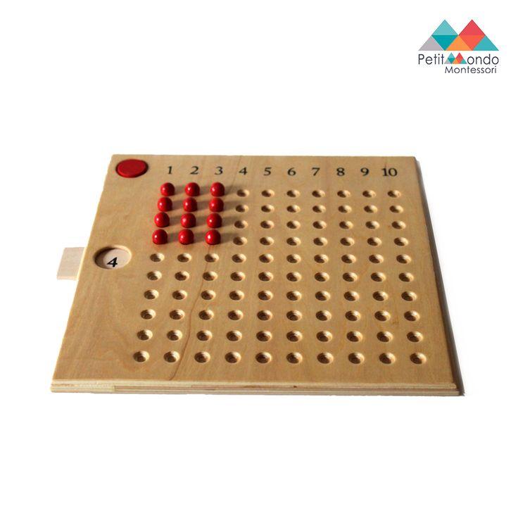 1 tabuleiro com 100 perfurações em madeira natural numerado de 1 a 10 no topo.  100 contas de cor vermelha. 9 placas individuais numeradas de 1 a 10.
