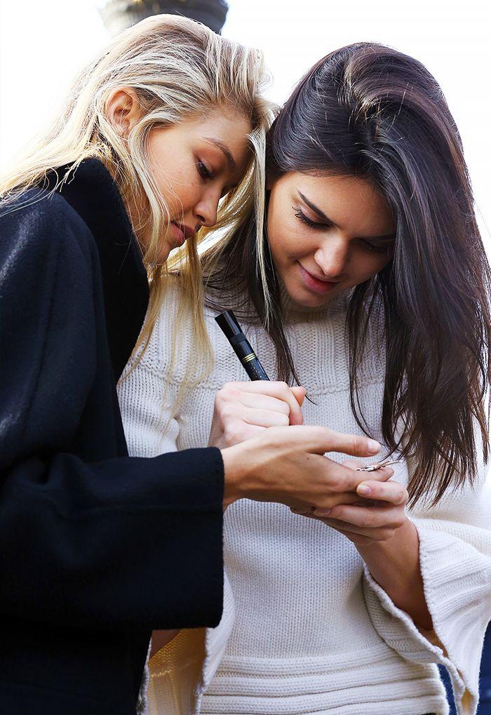 Kendall Jenner wears a white sweater, Gigi Hadid wears a black coat