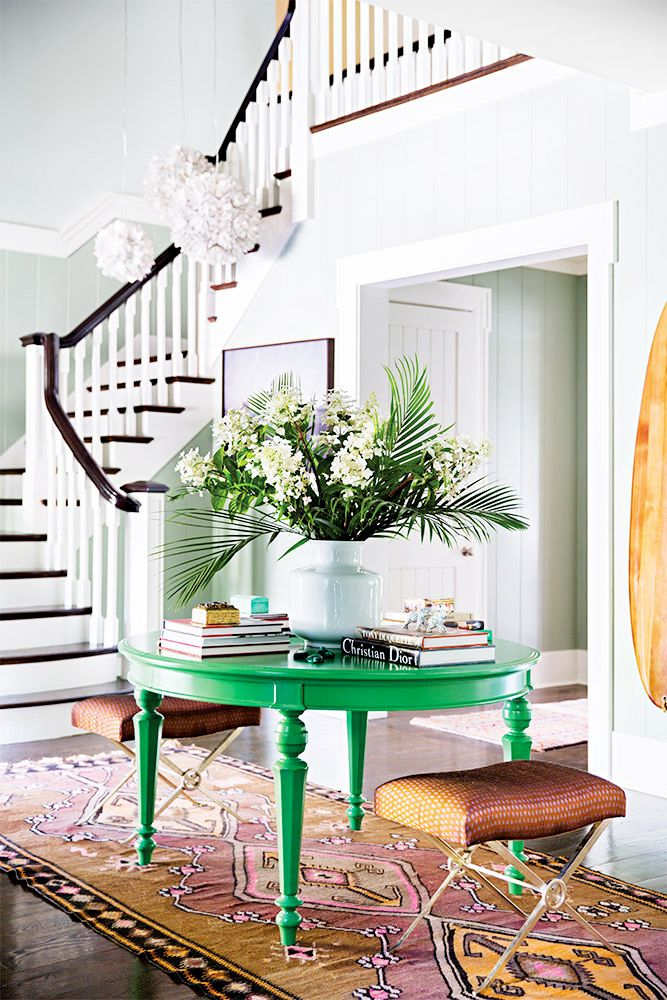 White foyer/entryway with gorgeous staircase and modern light fixtures // flowers