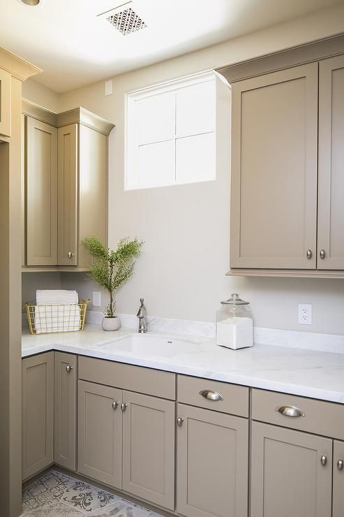 Light brown shaker cabinets accented with satin nickel cup ...