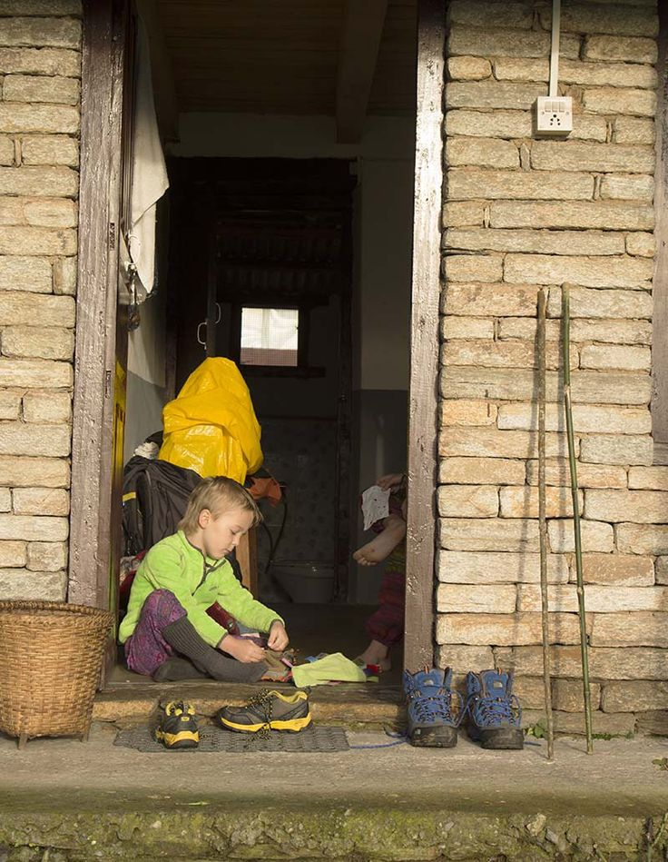 Child taking off shoes at Australian Camp, Nepal