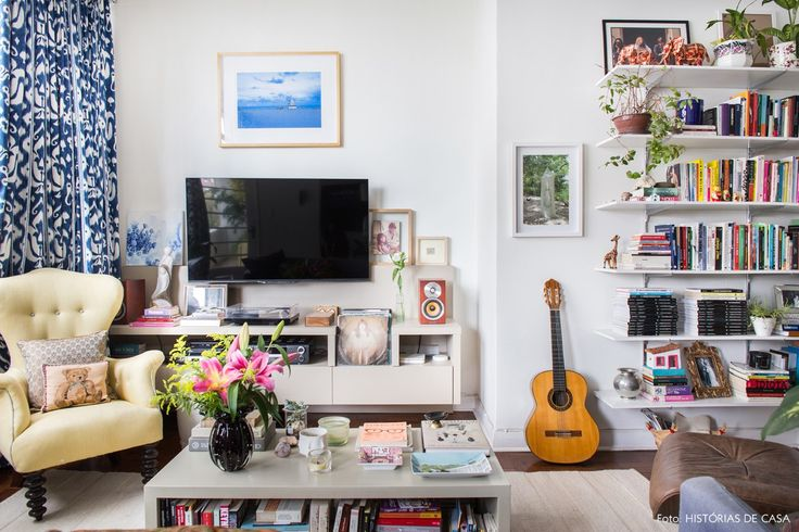 Sala de estar tem um mix de móveis no estilo high low e muitas estampas.