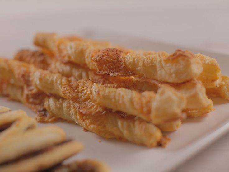 Cheese Straws recipe from Ree Drummond via Food Network.  Can serve immed, or freeze and reheat. She used FINELY grated cheddar.  You can use other types of cheese for a variation.