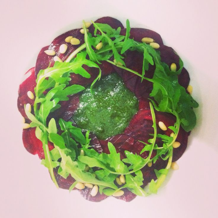 Beetroot carpaccio. Beets marinated in orange juice with basil pesto, pine nuts and rucola. Raw.