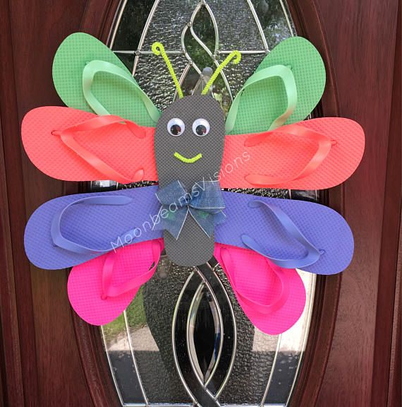 Unique flip flop butterfly wreath. This wreath is one of a kind and is sure to make your neighbors envious! It is made with 5 different pairs of flip flops, pipe cleaners, google eyes and a bow. This was so fun to make! Measurements are approximately 21 wide, 18 high and 3 deep. It can be hung indoors or outdoors! In the picture it is hung on the door with a command strip.