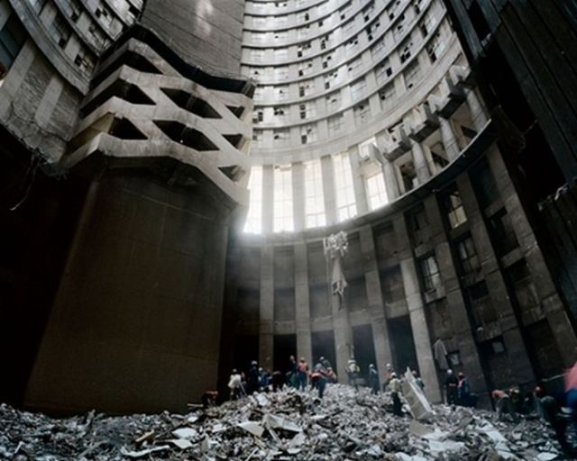 """Ponte City Apartments, built in 1975 in the Hillbrow neighborhood of Johannesburg, is 173 m high and the tallest residential skyscraper in South Africa. The original architectural plan provided a cylindrical shape of the building with a hollow interior named """"core.""""  Criminal activity gradually turned the once cosmopolitan Hillbrow into a gangland. By the end of the 90s many gangs moved into the Ponte City, devastating it and leaving 5 stories high pile of debris in the """"core."""""""