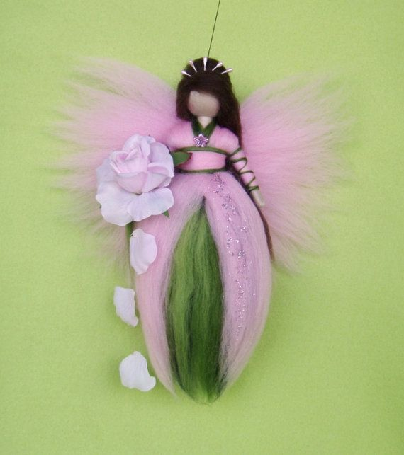 BEAUTIFUL ROSE FAIRY The doll is handmade by my needle felt soft sculpture technique. Her measure is approximately 8 heigh. She comes in light pink and green colours with brown hair and a little bit of glimmering fairy dust at her dress. She holds a fabric rose in the hand.  All my figures are handmade with wool and a pipe cleaner in their arms. They are made with lovely details and great care, but they are only for decoration and not for children to play with!  This dolls will enchant a…